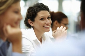 A woman sits amongst colleagues at a business meeting