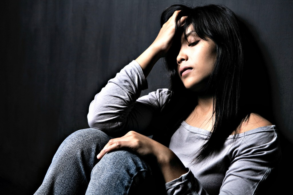 young woman looking upset slouches against a wall, holding her head