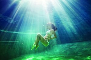 in a dreamy depiction of pregnancy a pregnant woman floats underwater holding her belly