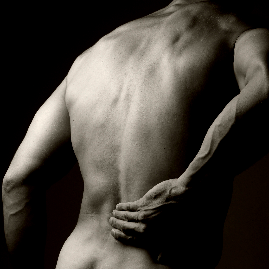 a man holds his back in a posture of pain