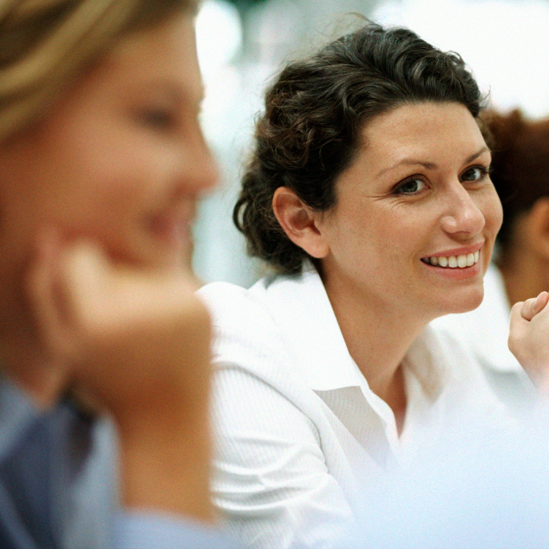 a woman in a white shirt at a business meeting with colleagues