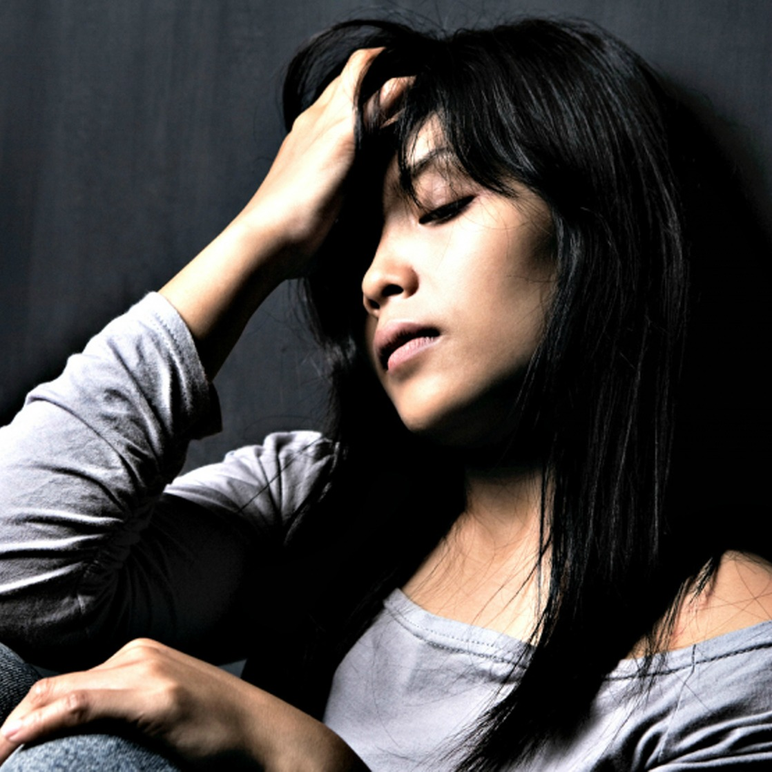 a stressed woman holds her hand to her forehead
